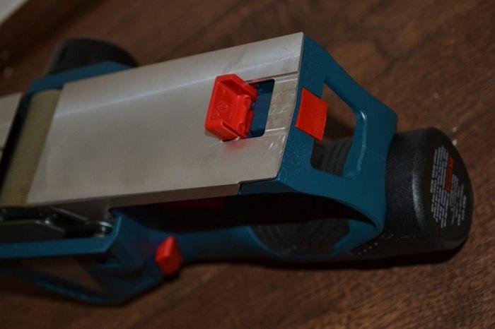 Откидная ножка на краю платформы подпружинена и приподнимает инструмент, чтобы случайно не повредить заготовку и защитить сами лезвия.